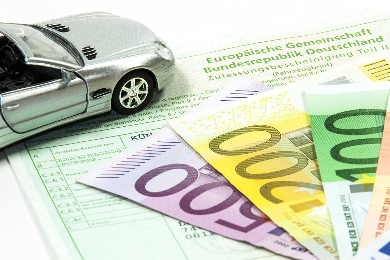 KFZ Zulassungsbescheinigung mit Geldscheinen und einen Auto